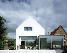 Architectuurcentrale Villa de Jong - typische kapwoning in modern jasje: strakke gevelafwerking, dakrand en kozijnen. De aanbouw contrasteert mooi met het witte huis.