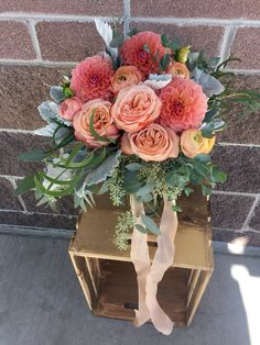 Bridal bouquet in soft coral, peach, dahlias, garden roses, cottage roses, ranunculus. Romantic wedding flowers.
