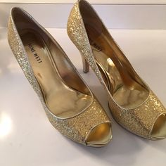 NINE WEST GOLD HEELS NINE WEST GOLD OPEN TOE HEELS. BEAUTIFUL AND VIRTUALLY PERFECT. NEVER WORN OTHER THAN TRYING THEM ON IN THE STORE WITH IS WHERE A COUPLE SMUDGE MARKS COME FEOM ON THE BOTTOM OF THE SHOE.  THE SHOES ARE A 8.5M Nine West Shoes Heels