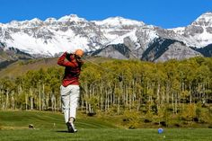A golfer swings for the snowy peaks of the San Juan Mountains - Telluride, CO