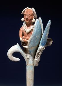 Nestled within the petals of a flower, an aged man, likely an ancestral figure, gazes straight ahead, arms folded gently over his abdomen. The vividly painted but delicate features are characteristic of Jaina-style ceramic figurines. The flower stem is hollow, and its open end functioned as the whistle's mouthpiece. The stem connects to the torso and head, which act as resonating chambers. The small size of the chamber produces a high, shrill sound.
