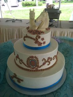 White chocolate horse toppers adorn a lovely wedding cake inspied by the lace on the brides dress.