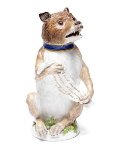 A very rare Meissen drinking vessel and cover in the form of a bear, circa 1750 - Probably modelled by J.J. Kaendler, naturalistically modelled and coloured in shades of brown, wearing a gilt-edged blue collar and holding a banner inscribed in puce-edged gilding 'Le vin est necessaire/ pour égayer, Il Vous donne, du la vie courage de la force/ et de l'esprit.', the base applied with leaves and flowers, 26cm high, crossed swords mark in underglaze-blue to rear edge of base