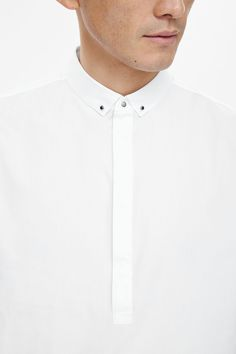 This shirt is made from a soft cotton poplin blend with small metal buttons on the collar and cuffs.