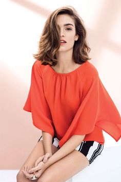 Bright and stripes! Orange batwing top worn with striped shorts. #stripes