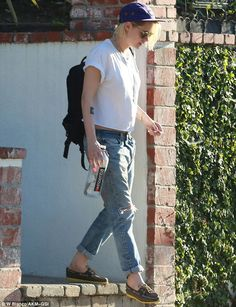 Keeping it casual: Kristen wore a simple white T-shirt, rolled up jeans and loafers, along with a baseball cap and large sunglasses