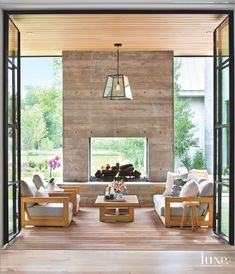 Steel-and-glass doors by Euroline Steel Windows & Doors fold open to the rear terrace and large courtyard. A board-form concrete fireplace—constructed by the project's builders, Matthew Pierce and Stephen Stone—anchors the terrace. The teak sofa, armchairs, coffee table and pendant are by RH. #rustichomedecor