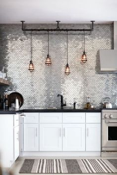 Small Kitchen Design with metallic countertop-to-ceiling backsplash, white shaker cabinets, industrial-style pendant light and stainless steel appliances.