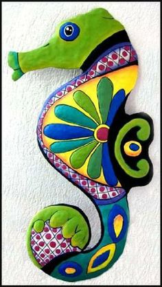 """Green & Blue Seahorse Painted Metal Wall Hanging - 13"""" x 24"""" . $36.95. Hand painted metal seahorse wall hanging. Can be used both indoors and outdoors. The seahorse is hand cut from recycled steel drum. The details of the design have been hammered into a bas-relief to accent the painted decorative designs. The choice of rich colors is especially attractive. The painting style is similar to that found on Spanish & Mexican talavera pottery."""