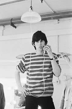 Keith Richards uses an electric shaver plugged into the socket of a ceiling light, 1962. Photo by Terry O'Neill