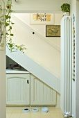 Looking at a white staircase with built in cupboard in a niche and with dog dishes
