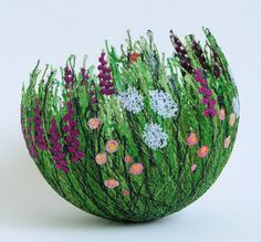Textile artist Anne Honeymoon creates these bowls that depict hedgerows, gardens, woodland flowers. The work is done with machine embroidery.