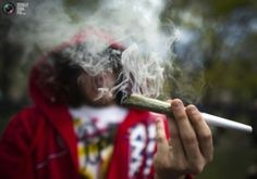 A woman smokes a large joint before The Global Marijuana March in Toronto, May 7, 2011.