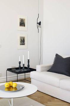 Flosin Parentesivalaisin on pariskunnan ensimmäisiä yhteisiä sisustushankintoja. Paino pitää valaisimen paikallaan. Musta tarjotinpöytä on Hayn. Tummanharmaat sohvatyynyt ovat matkamuisto Saint Tropezista.