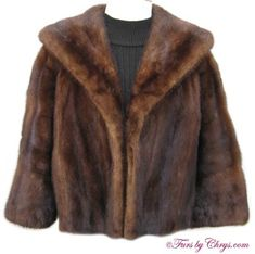 Vintage Mahogany Mink Jacket; #MM654; SOLD!; Very Good Condition; Size range: 10 - 14. This is a beautiful vintage genuine mahogany mink fur jacket. It has a Joseph Magnin label and features a gorgeous large shawl collar and 3/4-length sleeves with the pelts sewn diagonally for more interest. There are two exterior pockets. The lining is solid brown with an initial monogram in a similar color so it is discreet. It is an open design (no closures). This is a very versatile mink jacket!