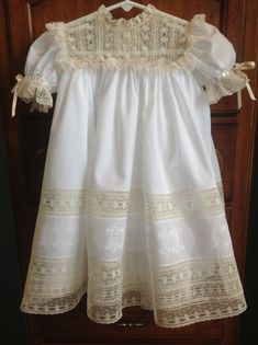 This beautiful dress is created using the finest white Swiss batiste and French Maline laces. The yoke is a square yoke made entirely of French