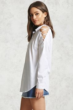 A woven shirt featuring a crisscross open-shoulder design, a partial button neckline, and long sleeves with button cuffs.