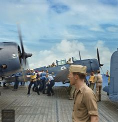 C: Deck crew spot checking Douglas SBD-5 Dauntless dive bombers of bombing squadron VB-12 on the flight deck of the U.S. Navy aircraft carrier USS Saratoga (CV-3), October 1943.
