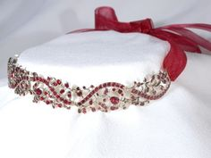 Early Georgian Garnet Necklace, Circa 1730-1750 – the motif is a ribbon and lyrical flowers. Asymmetrical in orientation, a sinuous band of garnets winds its way through the entire length of the necklace. Atop and bottom this are stems, flowers and leaves along with their arching stamens. Each stone is flat cut, with a planar top surface and just a few simple facets on each edge. Over 200 garnets bedeck the surface and provide warmth, light and fire.