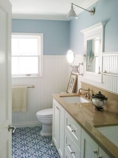A blue and white color palette brings a calm, coastal feel to this traditional bathroom. White wainscoting protects the sheetrock from daily family use and also adds character to the small space. Design by Courtney Blanton MP- like beadboard wanscotting Wainscoting Styles, Wainscoting Bathroom, Mirror Bathroom, Paint Bathroom, Black Wainscoting, Wainscoting Height, Painted Wainscoting, Wainscoting Panels, Master Bathroom