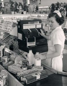A grocery store cashier rings in purchases at a store sometime in the 1950s.