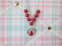A statement necklace with 10 mm red glass pearls with a focal love heart charm and tear drop glass pearls. The necklace is finished with convenient