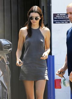 Kendall Jenner wears a halter grey dress with silver cat-eye sunglasses.