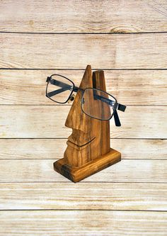 Decorative handmade stand for eyeglasses made of Plum tree. It is covered with natural transparent colorless wax that shows native wooden texture. Can serve as an interior adornment and will save your glasses from any damage.  Dimensions: width -85mm (3,5) height - 150mm (6) depth - 50mm (2)  Other wood products can be found here : https://www.etsy.com/ru/listing/280338562/stand-for-a-mobile-phone-stand-for?ref=teams_post