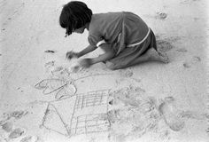Eve Arnold - CUBA. Cayo Carenero. Juana draws her dream house in the sand on the beach. 1954.
