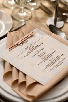wedding napkin folded into a simple square, then simply fold back the corners and place the menu on top. The reception staff could probably do this for you.