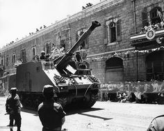 Tank with soldiers rolling through Jerusalem during a military parade