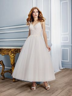 Moonlight Style T750 Detailed lace adorns this V-neck tea length bridal gown and elegantly cascades over your natural curves. The alluring low revealing back is accented with lace straps to finish this sweet retro bridal gown.