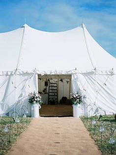 Hessian carpet leading into the marquee & milk churns filled with flowers at the entrance -   Image by Georgina Harrison - Rustic Marquee Wedding In Yorkshire With A Lavender And Dove Grey Colour Scheme With Bride In Cymbeline Of Paris Dress