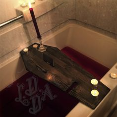 COFFIN BATH TRAY Life After Death Designs Coffin Bath Tray is made from solid wood, stained or painted in a finish of your choice and sealed in water resistant clear lacquer. Bath tray comes with two detached feet, or stops for the outside edges of the tub. Feet will come with industrial strength adhesive backing for you to place underneath the tray to prevent slipping, and ensure a perfect fit! Instructions will be provided. Bottom of tray is also coated in a slip resistant spray for grip…