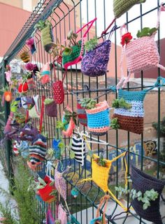 This picture is great ! Really funky knitted planters ! All is there, colors, seed bombing, urban environment !