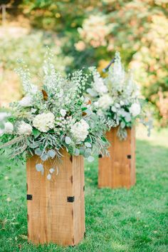 similar arrangement in white with greenery placed behind chairs at beginning of aisle
