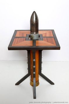 Stockpile Designs takes old, unused military waste, such as rusty bombshells and empty canisters, and turns them into home decor. Seen above is the Silo End Table with a dummy WWII Naval round used as the base.