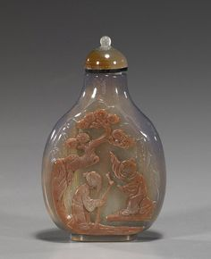 Chinese Carved Chalcedony Agate Snuff Bottle  Very finely hollowed, Chinese nearly transparent gray chalcedony agate snuff bottle; with some moss-like inclusions and with cameo-carved sard color figures and pine, matching stopper; H: 3""