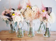 the mason jars as vases filled with flowers coordinating with wedding colors and used as table decorations