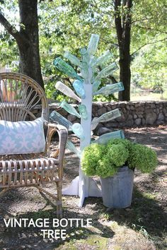 If you've got a collection of glass bottles, here's a great repurposing idea --- turn them into a vintage glass bottle tree! I love how it puts the beautiful aqua-colored glass on display!