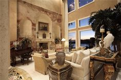 High ceiling living room features extensive use of marble throughout. Large mantle holds candelabra and ornate clock, columns dominate the entrance, and dark wood piano compliments the light toned seating