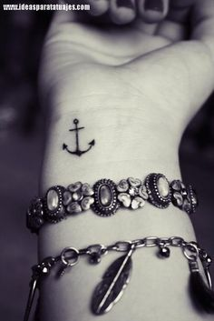 tatuajes de anclas en la muñeca de una mujer