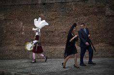 A man dressed as a Roman walks past a woman wearing the traditional mantilla next to the entrance gate of La Macarena church before a procession during Holy Week in Seville, Southern Spain, Thursday, April 21, 2011. AP / Emilio Morenatti