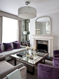 Shades of metallic silver glint in this amethyst and silver living room. The mirrored coffee table and French over-mantle mirror add an extra silver element.