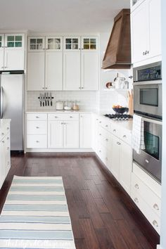 White Kitchen with wood range hood by The Lilypad Cottage