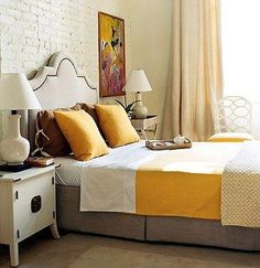 white brick, yello bedspread, yellowy art, upholstered headboard