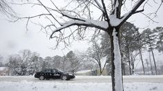 A vehicle moves along Jefferson Avenue as snow continues to fall on Thursday morning in Newport News. (Photo by Kaitlin McKeown / Daily Press)