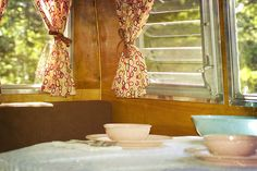 Trailer Interior, love the curtains and pink dishes! #vintage #trailer #travel