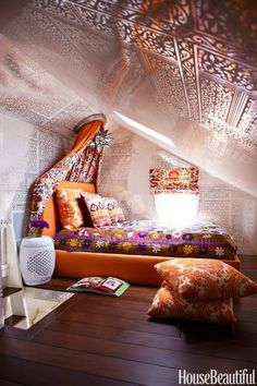 """It would have been a sad little attic-like space if we didn't make an effort to turn it into a super-groovy teenage girl's room,"" designer Katie Maine says of the space in a Newport Beach, California, house. She and designer Jason Maine swathed the room in Brunschwig's Bombay wallpaper, custom-printed on Mylar. Bed and canopy by Maine Design. Vintage suzani bedcovering from Yurdan. Moravian start light, Visual Comfort."