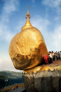 """The Golden Rock.  The Golden Rock at Kyaiktiyo, Myanmar, is a holy and important site which Buddhists frequent in large numbers. A gold leaf covered boulder precariously balances on the edge of a cliff, and pilgrims come to worship this astonishing defiance of gravity. It is said that a single Buddha hair exists under the rock.""  Photo by David Lazar, via Flickr."